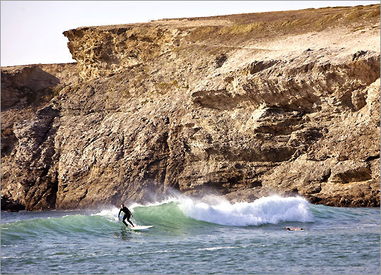 A surfer rides a wave beneath the cliffs of Belle-Ile-en-Mer.
