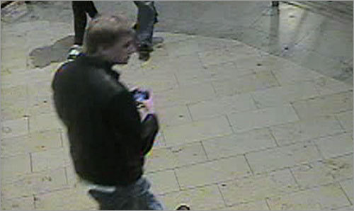 In this photo from the mall, the man again appears to have an electronic device in his hands.