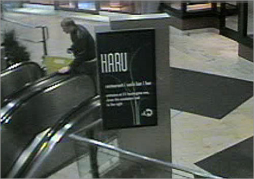 In this picture, the person of interest steps onto an escalator at the Copley Place Mall.