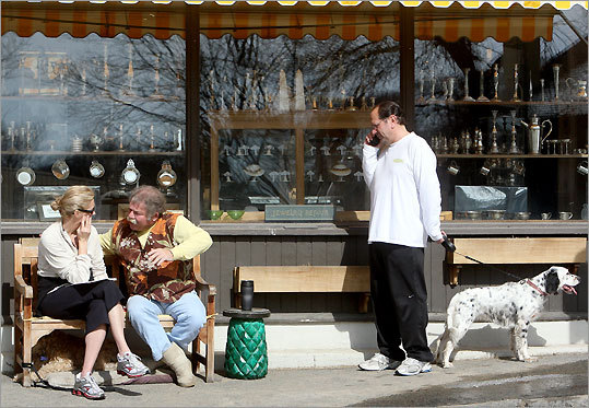 Robin Falzone, left, chats with Dana Dorfman outside his Union Street antiques shop while Robin's husband, Joe, takes a call.
