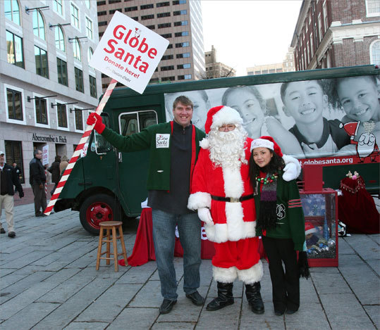 Dec. 10 in Boston Max Lane (left), former guard for the New England Patriots, and Tina Gao, radio show host for Magic 106.7, stayed outdoors for six hours on a brisk day in Faneuil Hall to hold signs and raise money for Globe Santa while also mingling with people. Learn more Make a donation