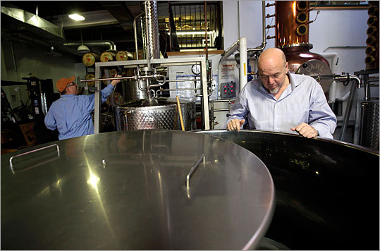 The production room at Dry Fly is dominated by stainless steel tanks, copper distilling equipment -- including a tower that rises three stories in the air -- and a wall of oak barrels marked 'whiskey.' Cases of finished booze are stacked everywhere. Here, Dry Fly employees check a batch of gin at the distillery.