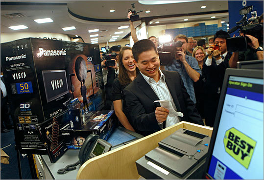 Brad Katsuyama, holding a receipt, and wife Ashley, become the world's first consumers to purchase a Panasonic Full HD 3D system at Best Buy in New York on Wednesday March 10, 2010.