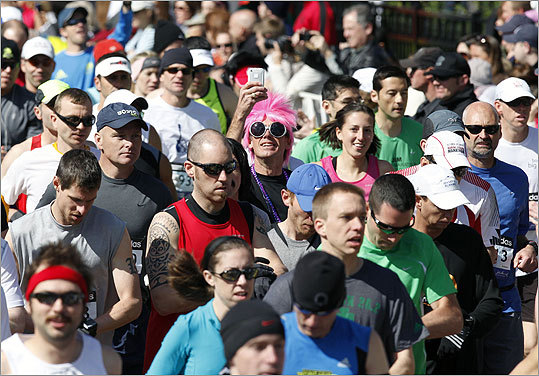 A runner adds some flair to the race by wearing a pink wig and large sunglasses at the general race start.