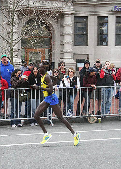 Spectators snapped photos and rang cowbells as the elite women runners came through Kenmore Square.