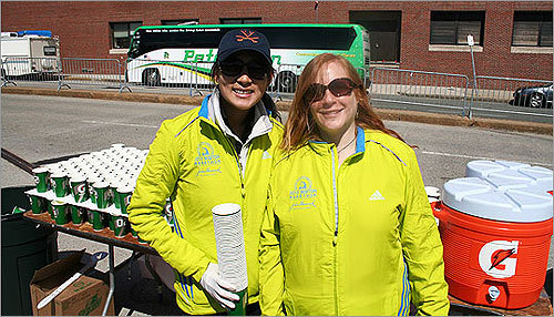 Lesley Park (left), visiting from Connecticut, and Marlene Smurzynski of Boston waited to pass out water to runners at mile 25 with other volunteers from the University of Virgina Club, an alumni association. Though Smurzynski said the weather was good for the runners, the wind almost caused a 'cup debacle.'