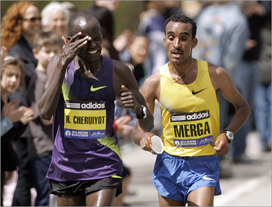 Robert Cheruiyot, of Kenya (left) wiped his face as he ran alongside Deriba Merga, of Ethiopia as the two passed a water station, in the Newton.