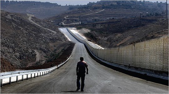 A man walks down the Israeli side of a divided highway around Jerusalem in 2007.