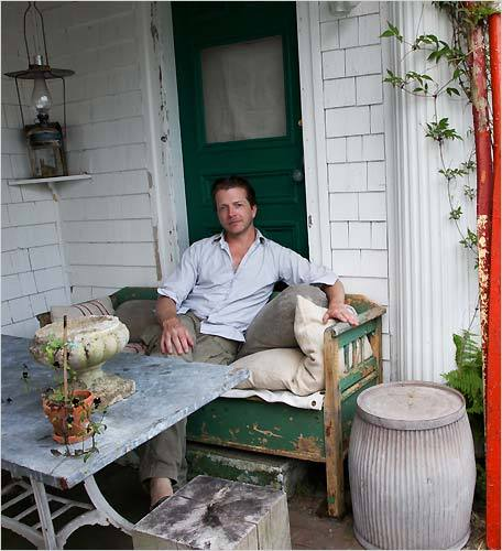 John Derien relaxes on antique grain sack bolster cushions by a galvanized table in the outdoor seating area of his home in Provincetown. Two 14-foot red vintage Chinese life saving boat oars lean nearby. The home is a restored 1789 sea captain's house on Commercial Street.