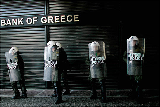 Riot police line up outside a closed branch of the National Bank of Greece during a 24-hour national strike in February, when Greek workers protested government cutbacks.