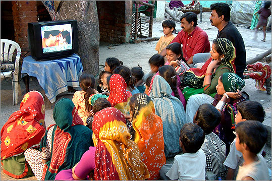 A group of people watched television at a slum in Gulbai Tekra, an area in the city of Ahmedabad in India.