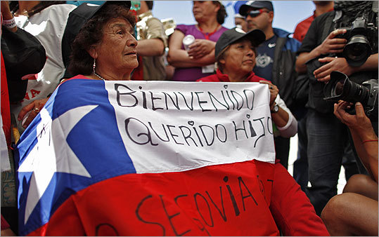 Margarita Rojo, left, mother of miner Dario Segovia, held a Chilean flag reading 'Welcome my beloved son' as she watched the rescue operation of her son at the camp outside the mine. Segovia was the 20th miner rescued from the mine.