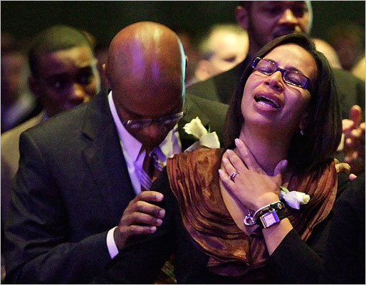 Angella Henry looked up as she was held by her husband.