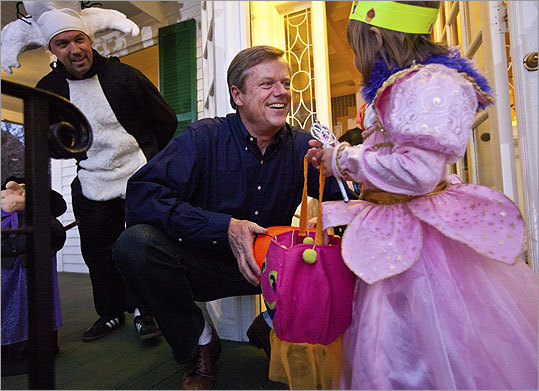 Republican gubernatorial candidate Charlie Baker (center) handed out candy to trick-or-treater Vivian Schaffnit, 4, outside his home in Swampscott. (Aram Boghosian for The Boston Globe)