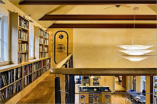 Above it all : A library loft makes practical use of the addition's vertical space. In contrast, the sitting area has a high ceiling and sightlines that run both vertically and horizontally.