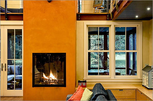 Handsome hearth : A tall, vividly painted fireplace helps divide the main seating area from the spacious screened porch.