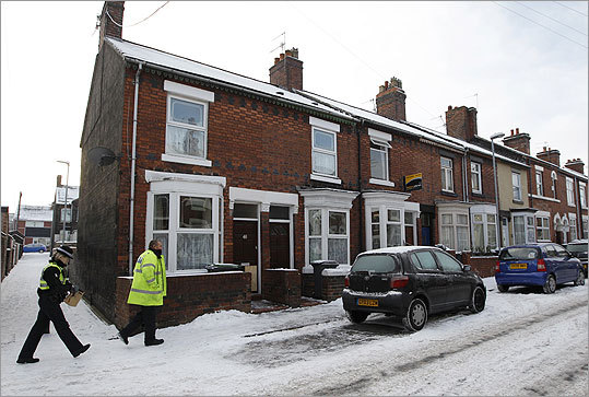 Police officers walked to a house that was being searched in Stoke-on-Trent in England. British police said 12 men suspected of preparing a terrorist attack had been arrested Monday during a series of dawn raids across England and Wales, including four from Stoke-on-Trent.