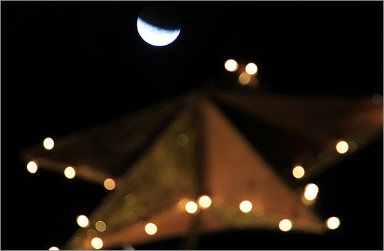 From beginning to end, the eclipse lasted about 3 hours and 28 minutes. The moon was seen over a Christmas tree during the beginning of the eclipse in San Jose, Costa Rica.