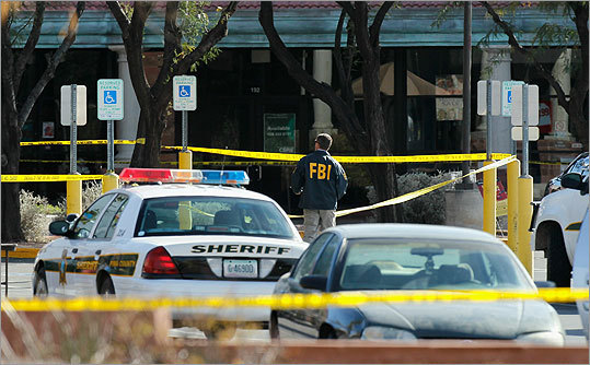 A day after the shooting, an FBI agent investigated the crime scene in front of the Safeway supermarket on the corner of West Ina and North Oracle roads where a gunman opened fire on a group of people. The suspect, Jared Loughner, 22, allegedly shot Giffords in the head during a public event entitled 'Congress on your Corner.'