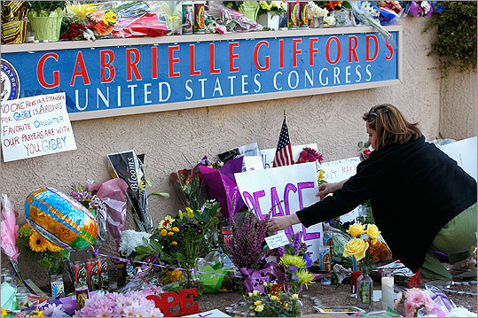 A woman repositioned a sign at a makeshift memorial outside of the district office of Representative Giffords a day after the shooting.