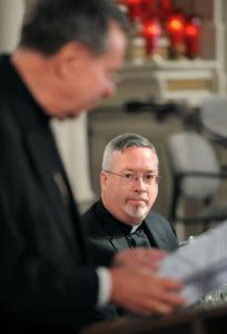 The Rev. Christopher J. Coyne listened yesterday as Archbishop Daniel M. Buechlein of Indianapolis announced that Coyne had been named auxiliary bishop.