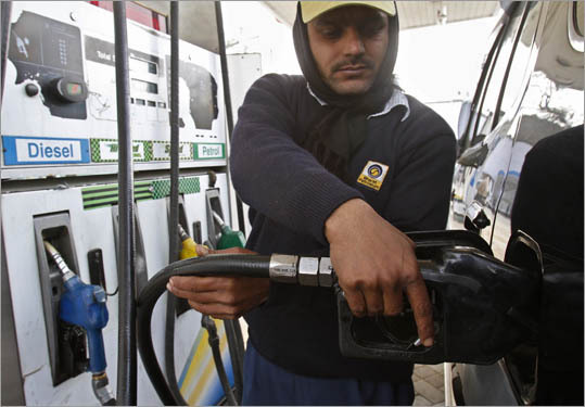 A man fills a vehicle with diesel at a fuel station in New Delhi