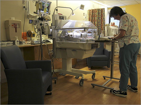 Debbie Connolly, an RN in neonatal intensive care works with a patient. A rocking chair is placed there for a mother or family member to be present.