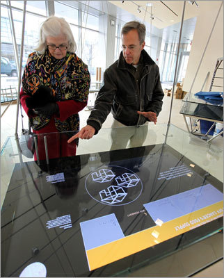 Terry Stone, left, MIT's executive vice president and treasurer, is shown a display by James May, senior project manager on MIT's facilities team. Five electronic display cases, in the Philip Alden Russell (1914) East Gallery, highlight the institute's five research focus areas.
