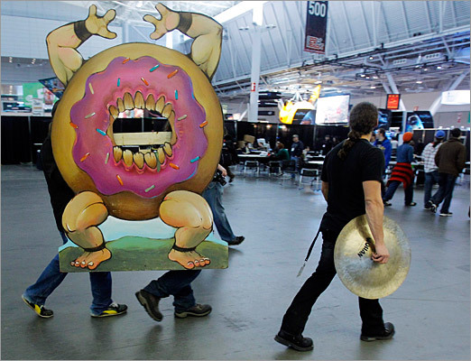 Members of the band Powerglove carry their 'Donuto' prop through the exhibition hall at the PAX East gaming conference on Friday.