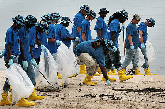 Oil cleanup workers picked up oily globs as they removed residue washing ashore on July 1, 2010 in Pascagoula, Mississippi.