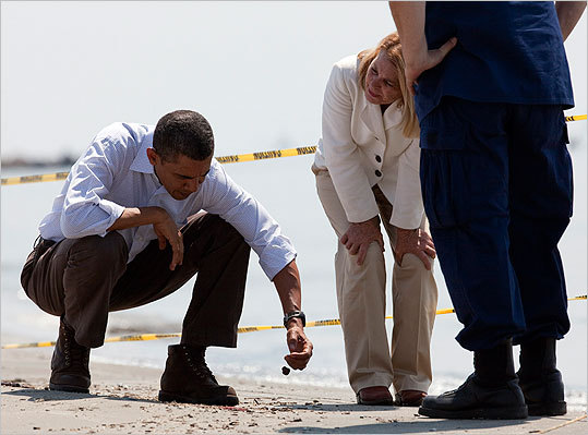 President Barack Obama (left) picked up a 'tar ball' as LaFourche Parish president Charlotte Randolph (center) and US Coast Guard Admiral Thad Allen, National Incident Commander for the BP Deepwater Horizon oil spill, looked on during a tour of areas impacted by the Gulf Coast on May 28, 2010.