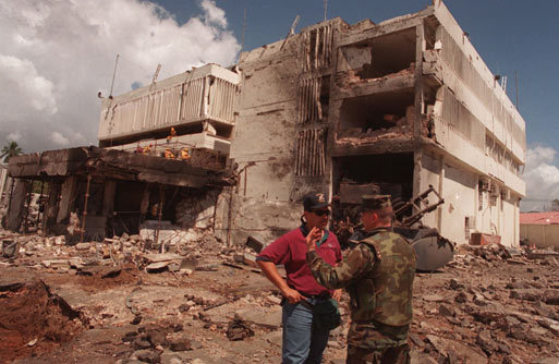 In this Aug. 15, 1998, file photo, a US Marine spoke with an FBI investigator in front of the damaged US Embassy in the capital Dar es Salaam, Tanzania. At least 200 people were killed and more than 1,000 injured during terrorist bombings at US embassies in Tanzania and Kenya. US officials believe bin Laden was also responsible for these attacks.