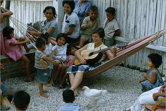 A Peace Corps volunteer sat in hammock and played guitar with villagers in Tarqui, Ecuador.