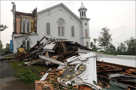 The steeple of The First Church of Monson laid in rubble on the ground after a tornado swept through.