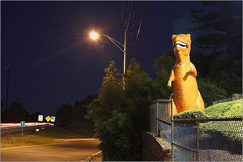 An orange Dinosaur watched night traffic at mini golf.