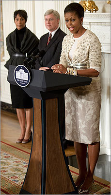 Mrs. Obama wore a mix of patterns and textures in this cream-colored ensemble featuring a belted J. Crew cardigan and a skirt by Rachel Roy. Mrs. Obama spoke at a preview of the dinner in the State Dining Room of the White House on Nov. 24, 2009. Also pictured, former White House Social Secretary Desiree Rogers (left) and and White House Curator William Allman.