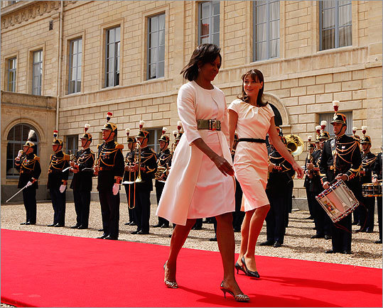Mrs. Obama strode into an arrival ceremony with Carla Bruni-Sarkozy, wife of the French president, on June 6, 2009, wearing a crisp white Michael Kors coat and wide Givenchy belt over a Narciso Rodriguez dress.