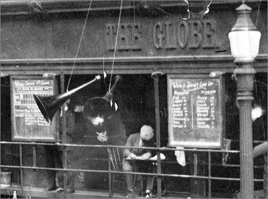 Oct. 8, 1925 Closeup: Globe staffer in a newsboy cap took notes on the storefront scaffold during the 1925 World Series. One blackboard listed the team lineups, another the box score.
