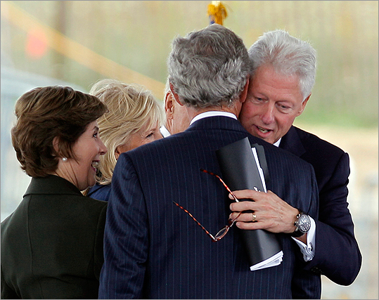 Former President Bill Clinton hugs former President George W. Bush after speaking during the dedication ceremonies.