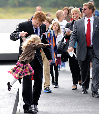 Lyra Nacke, 2, got a hand from her father Dale as she jumped off a wall at the Flight 93 Memorial before the dedication ceremony. Dale Nacke's brother Louis was one of the passengers who died on Flight 93