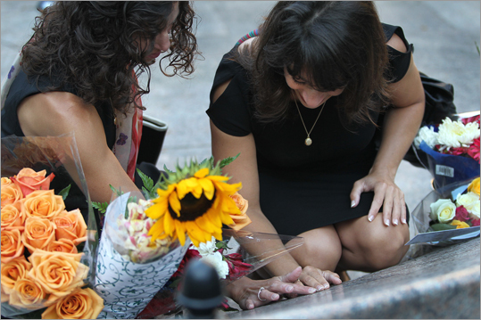Danielle Lemack, of Belmont, left, and Carie Lemack of Framingham, lost their mother, Judy Larocque of Framingham on American Flight 11. During Sunday's remembrance, the women touched their mother's name, engraved on the memorial stone in the Boston Public Garden.
