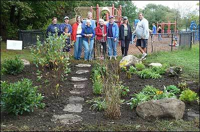 Volunteers create rain garden to protect Spy Pond