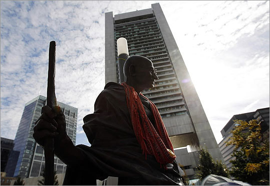 A statue of Mahatma Gandhi stood in the Occupy Boston encampment with Boston's Federal Reserve Building in the background.