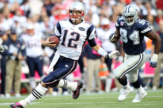 Tom Brady (12) of the New England Patriots carried the ball as DeMarcus Ware (94) of the Dallas Cowboys defended.
