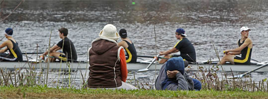 A couple of spectators relaxed on the Storrow Drive side of the river as some rowers loosen up on the water in front of them. The final day of competition in the 2011 Head of the Charles Regatta was Sunday.