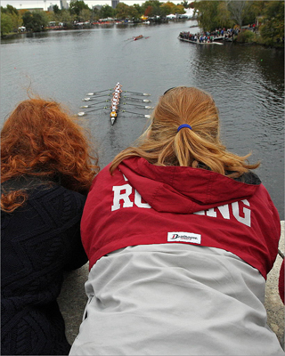 Spectators watched the Collegiate Women's Eights as they came out from under the Eliot Bridge.