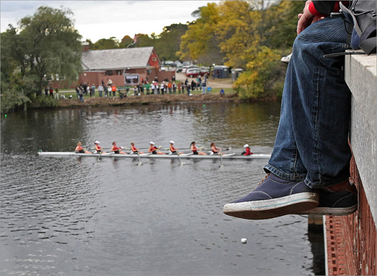 One spectator hung her feet over the wall as she watched competitors in the Collegiate Women's Eights come out from under the Eliot Bridge.