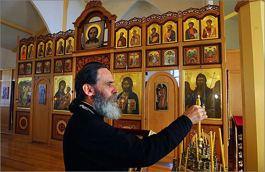 The Rev. Patrick Tishel of the Holy Resurrection Orthodox Church, which opened in 1876, lighted candles in front of the hand-painted saints on Harvard Avenue. 'Allston and America is a good place to learn to love each other and humanity,' he said.