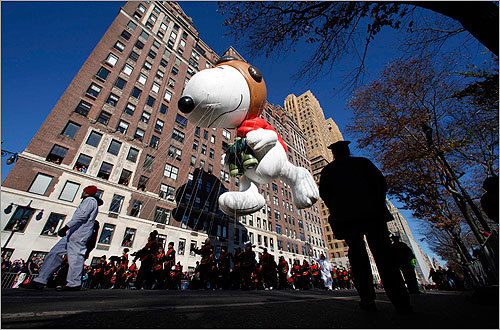 Delighted crowds gathered Thursday for Macy's Thanksgiving Day Parade on the streets of Manhattan under brilliant sunshine. Millions more viewed the live broadcast of the annual holiday production on television from the comfort of their homes. At left, the Snoopy the Flying Ace balloon floated down Central Park West during the parade.