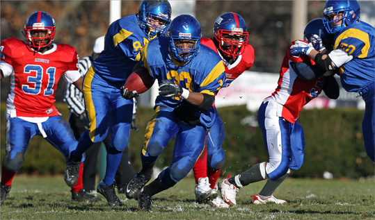 East Boston running back Andre Rickerson (33) broke free for some first half yardage. East Boston played South Boston in a Thanksgiving Day game at White Stadium.